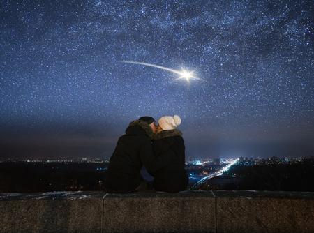Romantische avond. Liefdevolle paar zoenen. Nacht in de stad. Meteoor in nachthemel