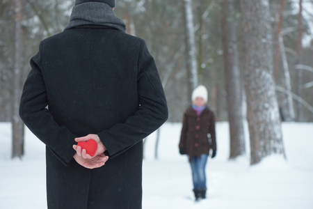 love confession: Surprise Valentines Day. Decorative heart in hands of Man. Meeting couple in winter park