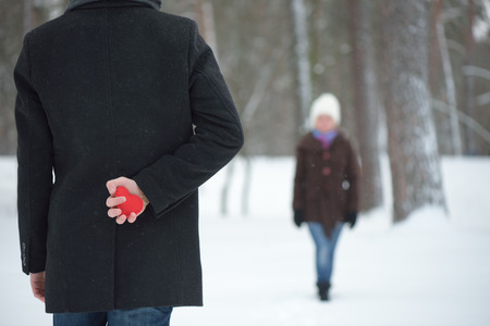 love confession: Surprise Valentines Day. Red decorative heart in his hand Man. Winter day in park