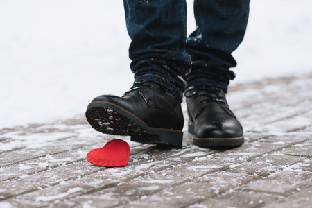 stepped: Tramples love. Symbol of separation. A man stepped on a shoe decorative heart Stock Photo