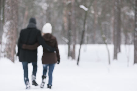 photo story: Love story in park. Couple walking outdoors embracing. Photo in defocusing