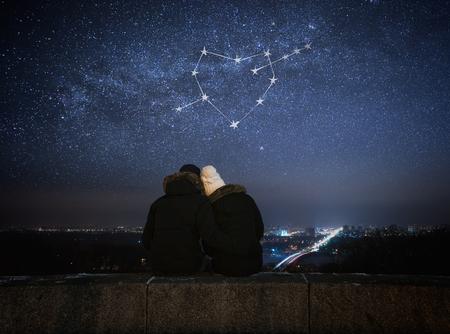 Carte Saint Valentin. Couple dans l'amour en regardant les étoiles. Nuit dans la ville. Constellation en forme de coeur
