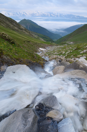 highland: River in the mountains. Summer landscape a cloudy morning. In the background fog and tops in the snow. Caucasus, Georgia, Zemo Svaneti. Water is blurred due to long exposure shutter camera Stock Photo