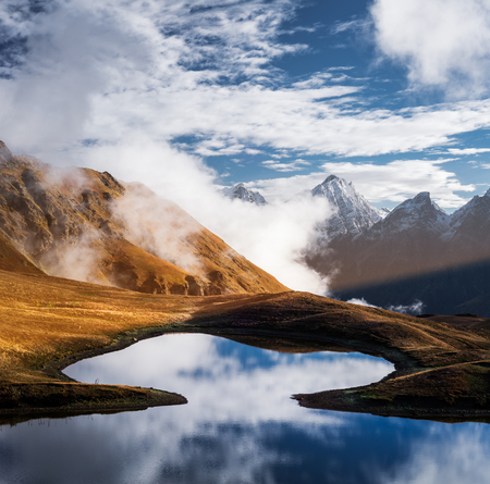 sky reflection: Highland Lake. Mountain landscape with tops and clouds. Reflection of the sky in water. Beauty in nature. Main Caucasian ridge. Koruldi lake, Zemo Svaneti, Georgia. Color toning