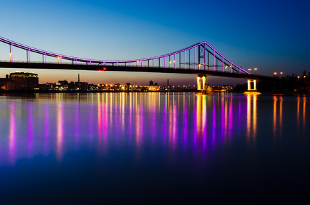 Night landscape. The city of Kiev, Ukraine, Europe. Pedestrian bridge across the Dnieper River. Beautiful lighting and reflection in water Фото со стока
