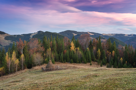 paisaje de otoño al atardecer. Haystack en el prado en un pueblo de montaña. Cielo con nubes hermosas. Cárpatos, Ucrania, Europa Foto de archivo