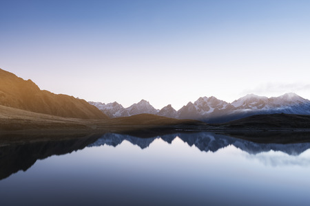 jezior: Mountain Lake. Morning landscape with clear sky and sunshine. Reflection of a mountain range in water. Main Caucasian ridge. Koruldi lake, Zemo Svaneti, Georgia. Color toning