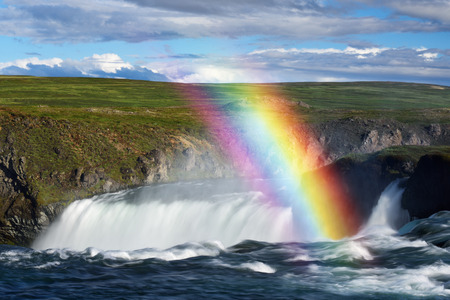 Summer landscape in Iceland, Europe. Godafoss waterfall and rainbow. Sunny day with beautiful clouds Stock Photo