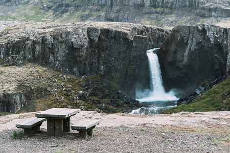 art processing: Tourist observation deck with wooden table and bench. View of beautiful waterfall in the mountains. Southeastern Iceland, Europe. Art processing of photographs, color toning