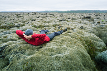 lava field: Man traveler in red jacket lying on the moss. Lava field on the south coast of Iceland, Europe. Tourist attraction. Amazing in nature. Cloudy summer day