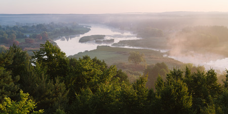fog forest: Summer landscape with the beautiful river and morning fog. Deciduous forest on a hill. Ros river, Ukraine, Europe Stock Photo