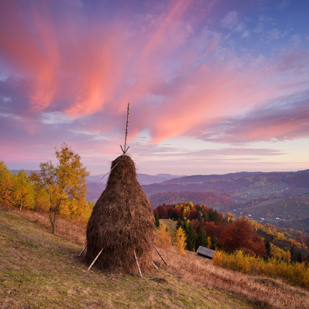 rural landscape: Autumn landscape with a beautiful sky and clouds. Stack dry hay in the meadow in a mountain village. Amazing dawn. Carpathians, Ukraine, Europe Stock Photo