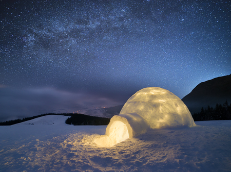 Night landscape with a snow igloo with light. Extreme house. Winter in the mountains. Sky with the stars and the Milky Way Archivio Fotografico