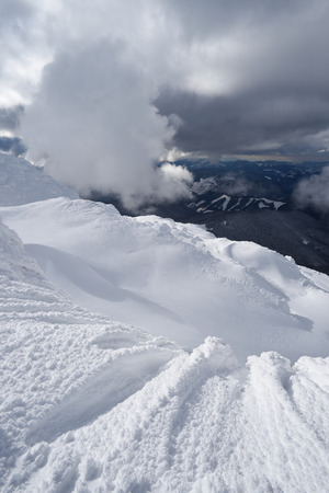 drifts: Winter landscape with a beautiful cloud. Snow drifts in the mountains Stock Photo