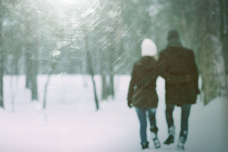 Love story in park. Couple walking outdoors embracing. Photo in defocusing. Color toning. The effect of old photos from scuffs and scratches photo