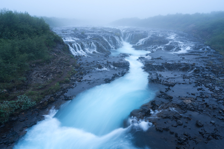 turquoise water: Landscape with an amazing waterfall Bruarfoss. Water is of turquoise color and beautiful cascades. Tourist attraction in Iceland. Morning fog Stock Photo