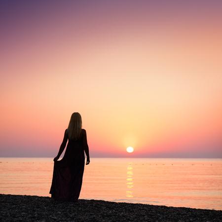 Blonde girl standing on the beach. Beautiful sunrise. Activities at the resort. Sea vacation. Turkey photo