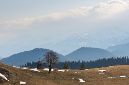 thawed: Spring landscape in the mountains. Old wooden chapel on a hill. Cloudy day