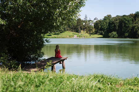 Blonde girl is sitting on a wooden pier. Summer vacation in a green park by the pond. Sunny weather photo