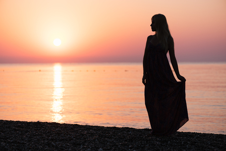 Silhouette of a blonde girl in a sundress. Beautiful dawn by the sea photo