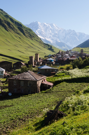 Summer mountain landscape with a snowy peak and a green valley. Old village with stone houses and medieval towers. Ushguli community. View of Shkhara Mount. Main Caucasian ridge, Zemo Svaneti, Georgia Stock Photo