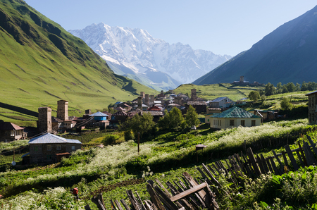 Mountain landscape with a snowy peak. The ancient alpine village. Sunny summer day with a clear sky. The village of Ushguli and Mount Shkhara. Main Caucasian ridge, Zemo Svaneti, Georgia Stock Photo
