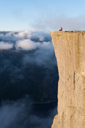 Preikestolen - amazing rock in Norway. Girl sitting on a cliff above the clouds. Pulpit Rock, the most famous tourist attraction in Ryfylke, towers over the Lysefjord Stock Photo