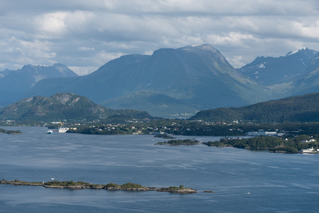 Norwegian landscape in summer. View from the mountain Aksla in the city of Alesund to the mountains of Skopphornet and Hundatinden, as well as the villages of Fyllingsjoen and Fiskarstranda