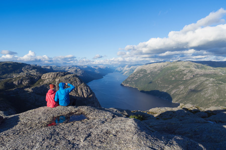 Pathway Pulpit Rock, Norway. Couple looks at the panorama of the Lysefjord. Sunny weather in the mountains Banque d'images