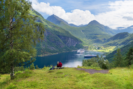 Geirangerfjord cruise. A fairytale by the fjord. Couple enjoys a majestic view in Norway. Near the tourist town Geiranger