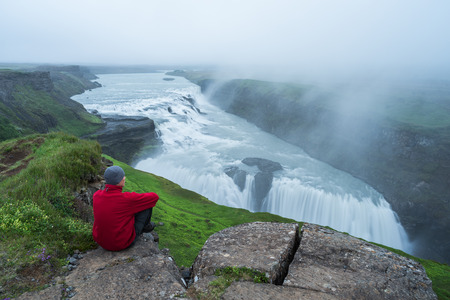Gullfoss waterfall in the canyon of the mountains. Tourist Attraction Iceland. Man tourist in red jacket sitting and looks at the flow of falling water. Beauty in nature