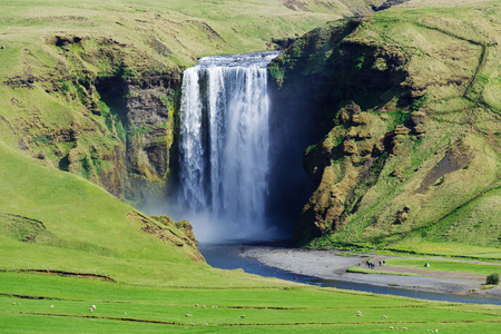 Skogafoss waterfall. Famous landmark of Iceland. Summer landscape on a sunny day. Camping with tents and many tourists