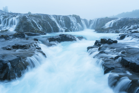 Bruarfoss waterfall. Water is of turquoise color and beautiful cascades. Tourist attraction in Iceland. Morning fog