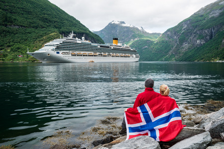 Sea cruise in Norway. Couple of travelers with a Norwegian flag look at the Cruise liner. Fjord Geirangerfjord near Geiranger city Banque d'images