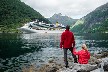 Cruise liner. Geirangerfjord near the town of Geiranger, Norway. Young couple of travelers on the shore of the fjord Banque d'images