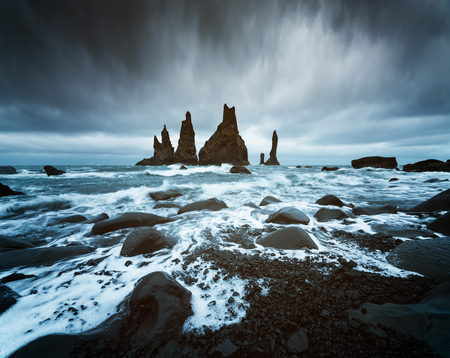 Trolls fingers. Reynisdrangar cliffs near the Vik town. Sullen landscape with the Atlantic Ocean. Tourist attraction of Iceland Фото со стока - 102697698