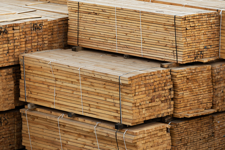 lumber in a large warehouse. Wooden boards in the stack Imagens