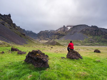 Volcanic landscape of Iceland. Tourist in a red jacket contemplates the beauty of nature Banco de Imagens