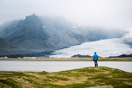 Tourist contemplates the beauty of nature in Iceland. View of the vatnajokull glacier near Breidarlon lake