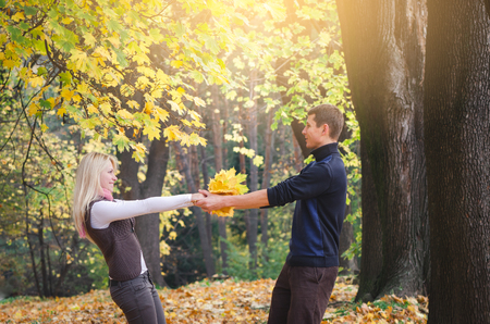 Loving couple is having fun. Walk in the autumn park. Young people at leisure