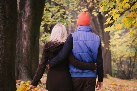 Couple in love goes embracing. Walk in the autumn park 版權商用圖片