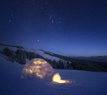 Night landscape with a snow igloo with light. Extreme house. Winter in the mountains. Sky with the stars Zdjęcie Seryjne