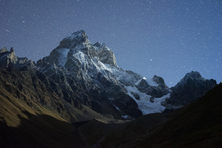 Night landscape. Starry sky over the mountains. Mount Ushba in the light of the rising moon. Main Caucasian ridge. Zemo Svaneti, Georgia Imagens
