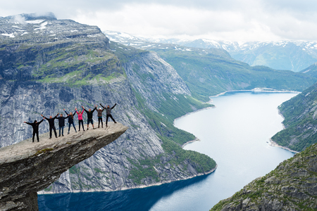 Norway, Odda, rock formation Trolltunga, July 18, 2017: group of tourists photographed on a rock