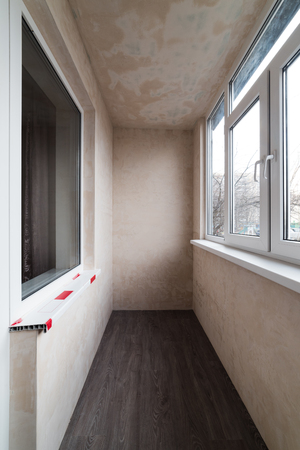 Repair of the balcony (loggia). Plastered walls of the room. Roughing work Stock Photo