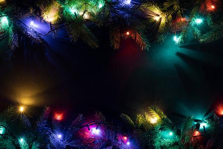 Fondo di festa di Natale con lo spazio della copia per testo. Anno nuovo concetto. Ghirlanda luminosa e decorazioni di rami di abete. Vista piana, vista dall'alto