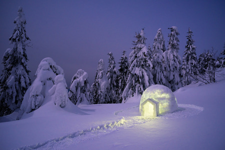 Snow eskimo igloo. Mountain hiking in winter. Night landscape with shelter for extreme tourists