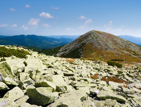 Mountain landscape with stones on the slope. Sunny summer weather. View on the mountain peak