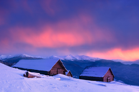 Winter in the mountain village. Old wooden houses covered with snow. Awesome sunset with beautiful clouds