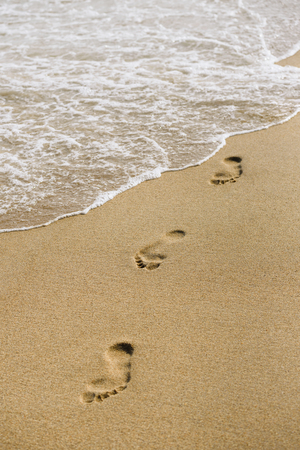 Summer background for design of sea resort. Footprints on a sandy beach. Sea Wave Foam in the Sand Stock Photo